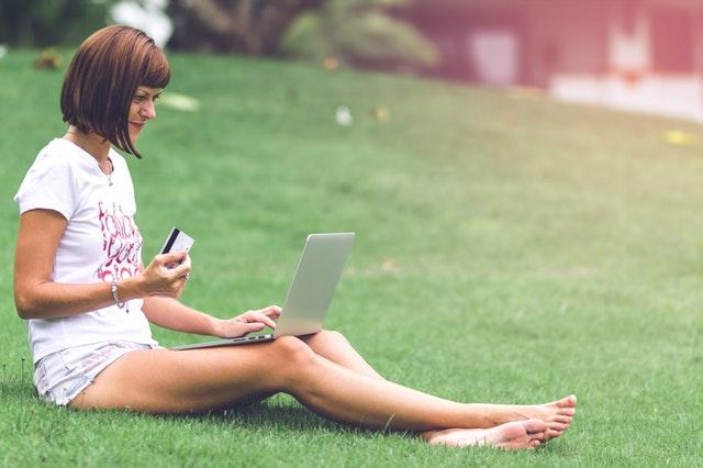 Žena s platobnou kartou v ruke sedí na trávniku a pozerá do notebooku.jpg
