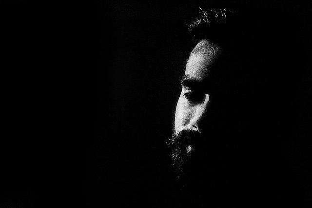 Muž s bradou, tmavé pozadie, depresia.jpg