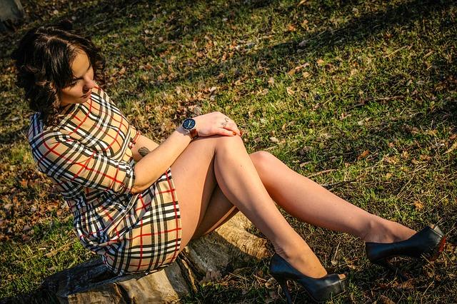 Žena v kockovaných šatách pozerá na svoje nohy.jpg