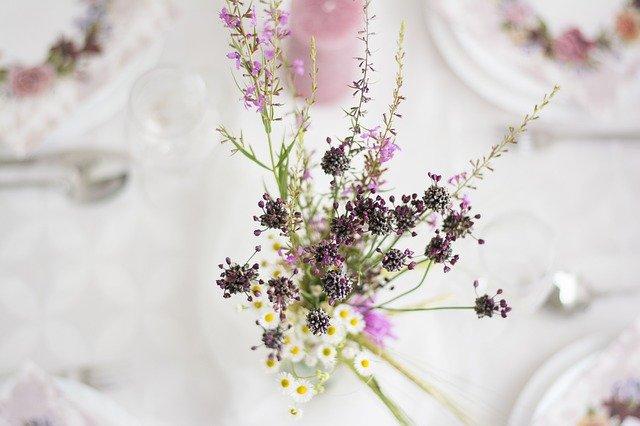 Svadobný stôl s vázou a fialovými kvetmi