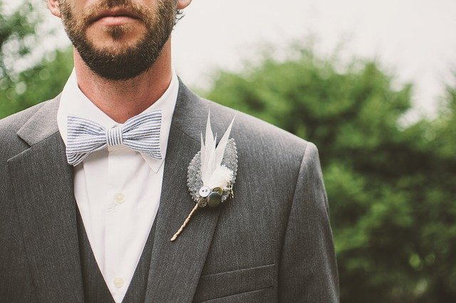 Ženích v sivom saku a svadobným pierkom na hrudi